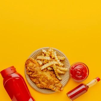Vista dall'alto di fish and chips con bottiglie di ketchup
