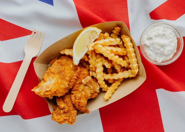 Top view of fish and chips with lemon slice and great britain flag
