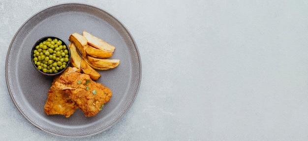 Vista dall'alto di pesce e patatine fritte con piselli su piastra e copia spazio