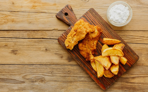 Top view of fish and chips with sauce on chopping board