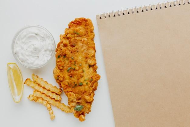 Vista dall'alto di fish and chips con salsa e notebook