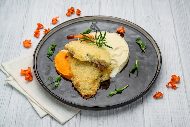 Top view of fish fillet in butter with mashed potato on wooden table, home kitchen