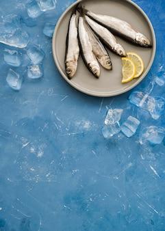 Вид сверху рыба на тарелке с ломтиками лимона