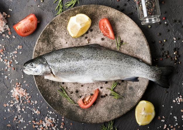 Вид сверху рыба на тарелке со специями