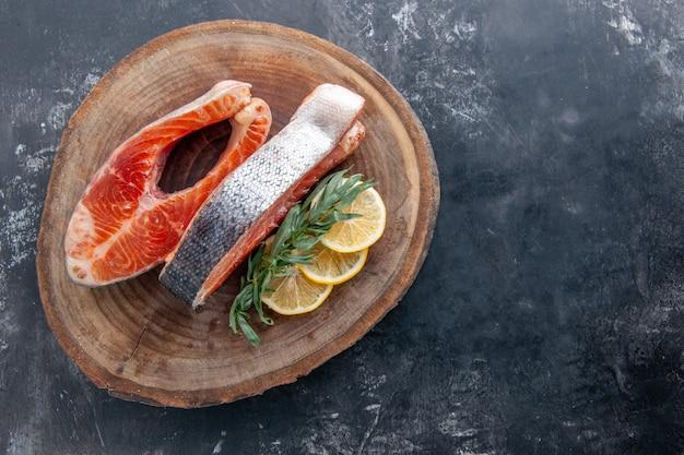 灰色の背景にレモンスライスと上面図の魚のスライス