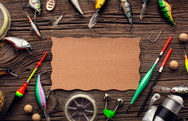 Top view of fishing equipment frame with colorful bait and piece of paper