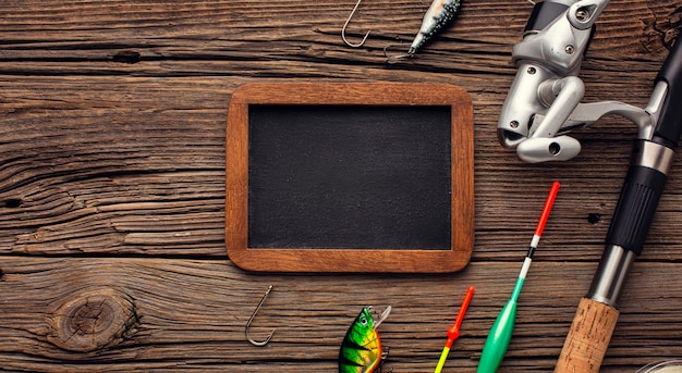Top view of fishing essentials with blackboard and copy space