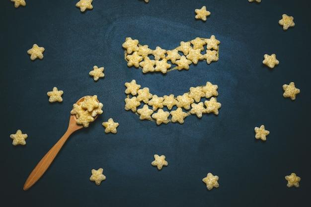 Вид сверху плоской планировки водолея, знак гороскопа из хрустящей кукурузной звезды на черном