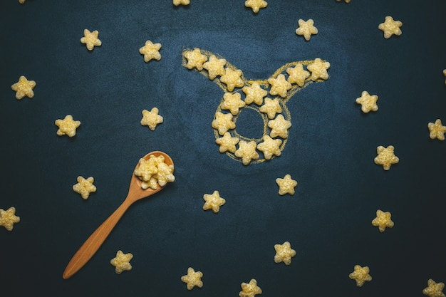 Top view flat lay aries horoscope sign made from crispy corn stars on a black