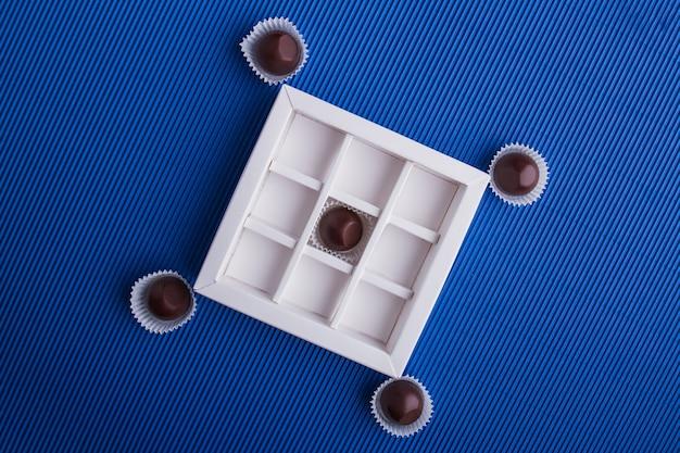 Вид сверху плоские коричневые шоколадные конфеты на синем фоне