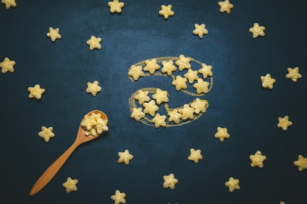 Top view flat lay cancer horoscope sign made from crispy corn stars on a black