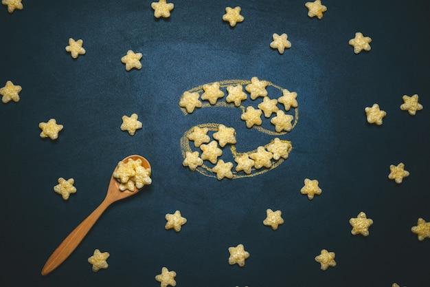 Вид сверху плоская планировка рак гороскоп знак из хрустящих кукурузных звезд на черном