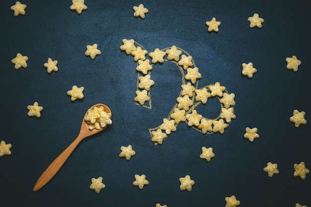 Top view flat lay capricorn, horoscope sign made from crispy corn stars on a black