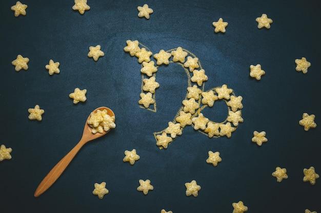 Вид сверху плоской планировки козерога, знак гороскопа из хрустящей кукурузной звезды на черном
