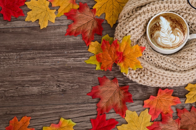 Top view, flat lay colorful autumn decoration with cup of coffee, scarf, maple leaves