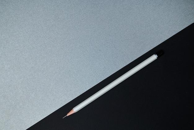Вид сверху . плоская композиция из офисных инструментов. серый карандаш и часть черной бумаги на сером фоне