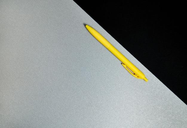 Вид сверху . плоская композиция из офисных инструментов. желтая ручка и часть черной бумаги на сером фоне