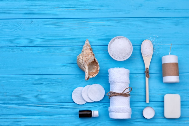 Top view flat lay concept of bathroom or beach accessories. blue wooden desk background.