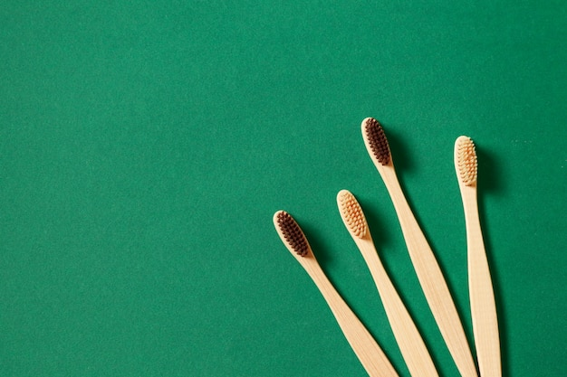Top view or flat lay concept with eco bamboo tree toothbrushes on green background