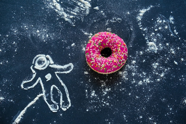 Top view flat lay creative still life with pink donut and spaceman made from flour on black