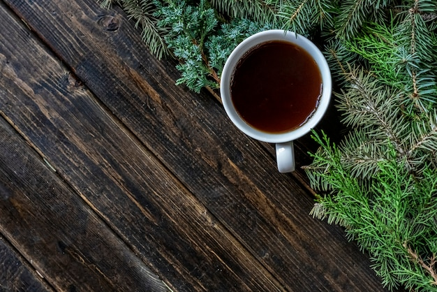 Top view flat lay cup of tea near pine branches on a wooden surface.