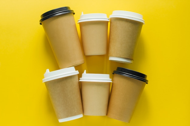 Top view flat lay disposable cups for takeaway drink on yellow