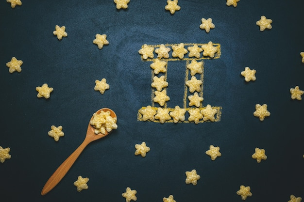 Top view flat lay gemini  horoscope sign made from crispy corn stars on a black