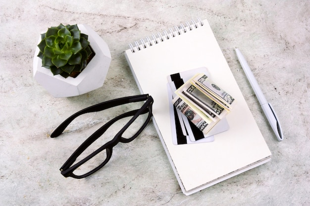 Top view flat lay notebook, pen, money,credit cards, glasses and succulent on a marble table