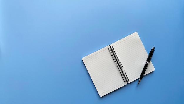 コピースペースのある青い背景に黒いペンと並んで空白のページのノートブックの平面図フラットレイ