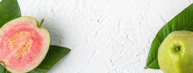 上面図、白いテーブルの背景に分離された新鮮な緑の葉とおいしい美しい赤いグアバのフラットレイ、コピースペースで撮影されたスタジオオーバーヘッドテーブル。