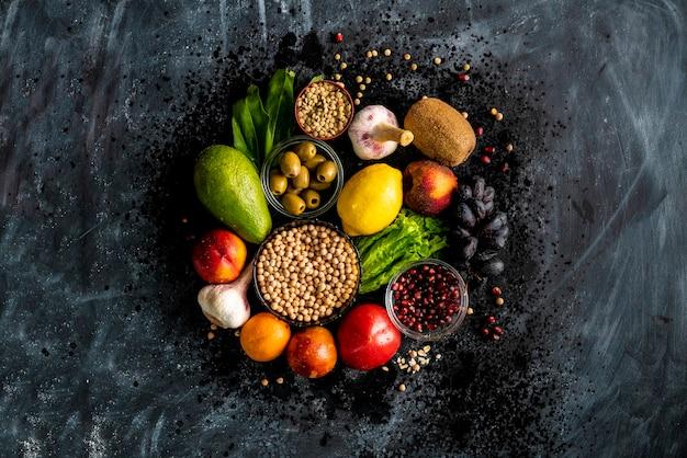 Плоский вид сверху выбора здоровой пищи с фруктами, семенами овощей и зелеными травами на столах