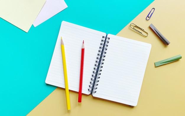 緑と黄色の色鉛筆ペーパークリップと鉛筆キャップ付きノートブックの上面図フラットレイ