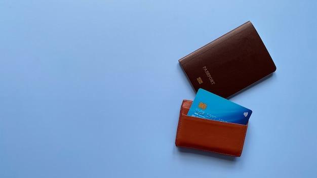 Плоский вид сверху паспорта и кредитной карты в держателе карты на синем фоне с копией пространства
