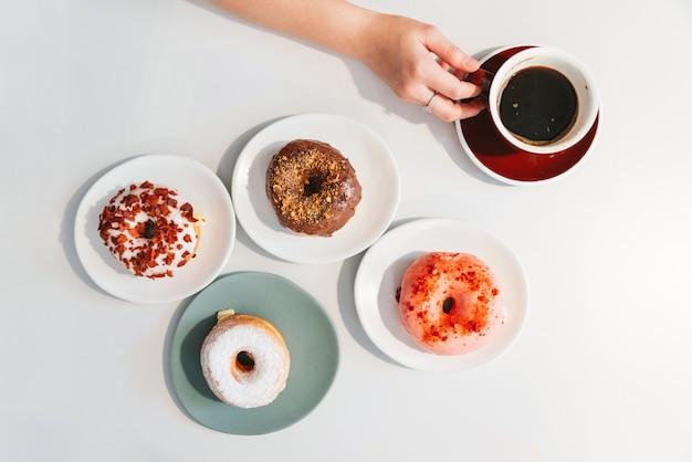 モダンなカフェのテーブルでアメリカーノのコーヒーのカップを持っている女性の手でストロベリーピンク、チョコレート、砂糖釉、ベーコンチーズドーナツの平面図(フラットレイアウト)。