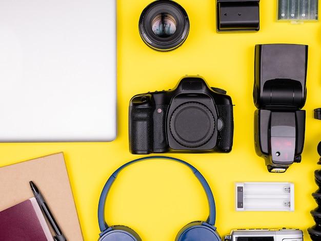 黄色の背景に旅行者のアクセサリーの平面図フラットレイ。デジタル一眼レフとアクションカメラ、ヘッドフォン、ラップトップ、パスポート