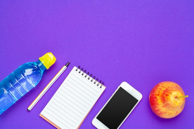 Top view flat lay of office supplies with water bottle background
