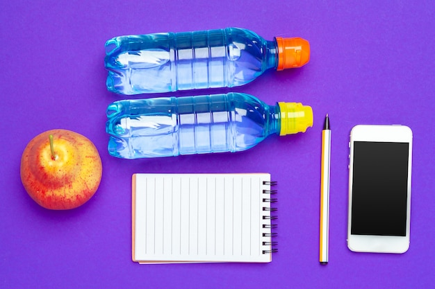 Top view flat lay of office supplies with water bottle