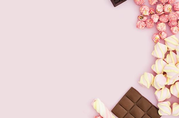 平面図、フラットはピンクの背景にさまざまなお菓子、キャンディー、マシュマロ、チョコレート、ポップコーンのセットの上に置く