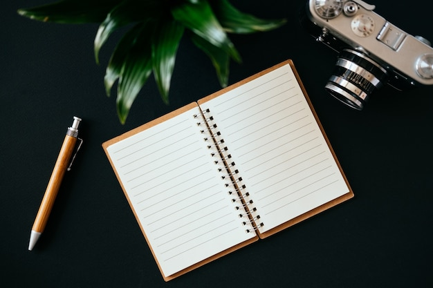 Top view of a flat lay open diary pen camera and green plant lies on a black table. concept of a blogger and journalist. place for text
