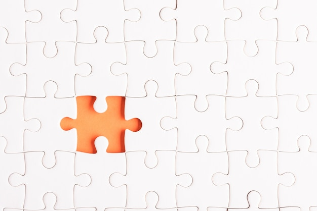 Top view flat lay of paper plain white jigsaw puzzle game texture incomplete or missing piece