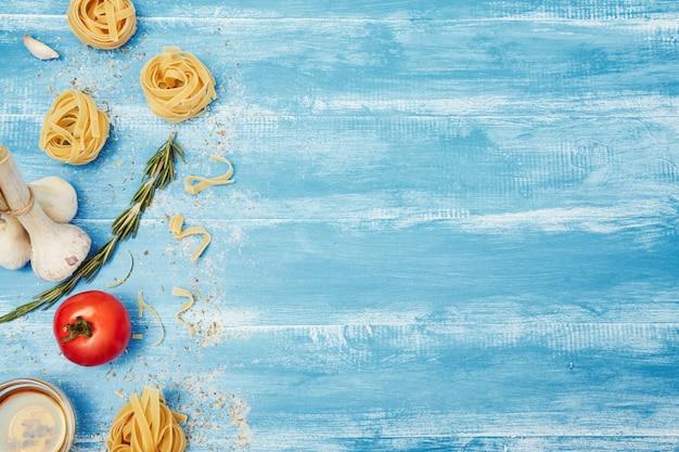 平面図、フラットレイアウト。パスタの巣、油、塩、コショウ、トマト、ニンニク、フォーク、青い木製のテーブル。