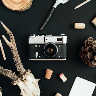 평면도, 평면 평신도 사진 작가 개념. 레트로 카메라, 염소 뿔, 수제 숟가락, 공예 일기, 검은 분필 보드 배경에 콘.