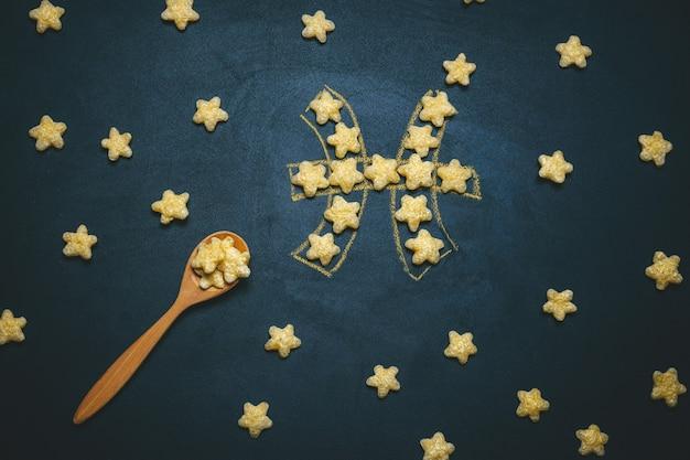Вид сверху на плоских лежащих рыб, знак гороскопа из хрустящих кукурузных звезд на черном