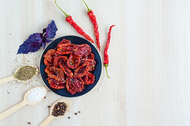 Top view, flat lay of plate with sun-dried tomatoes in olive oil, with spices, sea salt, provencal herbs, basil leaves on light background with copy space, place for text