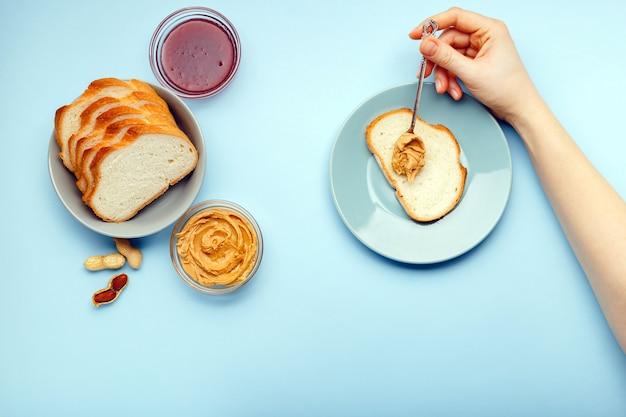Вид сверху, плоский процесс приготовления завтрака, намазывания хлеба, тостов с арахисовым маслом, сливочной арахисовой пасты женскими руками на синем фоне. подается с арахисовым маслом, арахисом в скорлупе, джемом