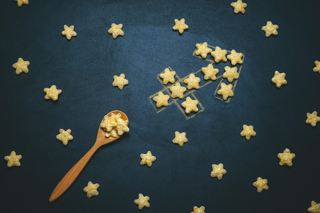 Top view flat lay sagittarius, horoscope sign made from crispy corn stars on a black