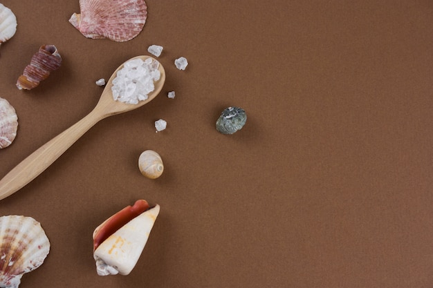 Top view flat lay sea salt spoon and sea shells brown background copy space