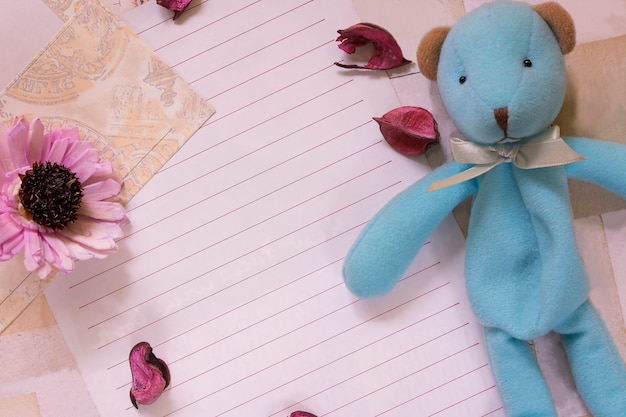 レター用紙の封筒と花びらのかわいいクマの人形の上面図フラットレイショット