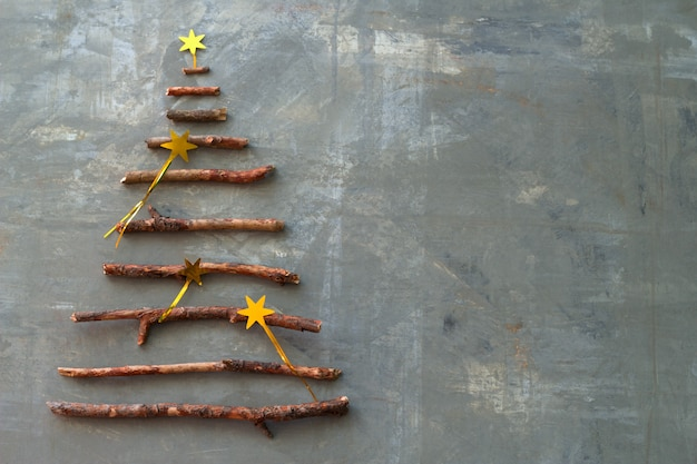 Top view flat lay silhouette of a christmas tree made of wooden twigs decorated with gold stars