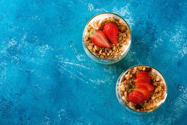 Вид сверху, плоские две стеклянные чашки с фруктово-ягодным десертом из манго и клубники с мюсли и ванильным кремом или рикоттой